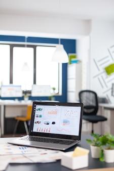 Nahaufnahme eines laptops im start-up-unternehmensbüro mit diagrammen und statistiken