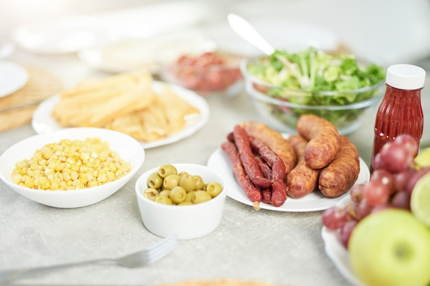 Nahaufnahme eines lateinamerikanischen frühstücks mit mais, oliven, salat und fleisch auf dem hellweißen küchentisch. morgen, frühstücksideenkonzept. selektiver fokus