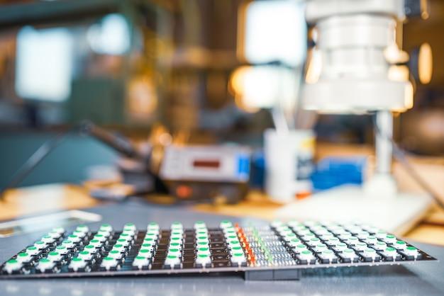 Nahaufnahme eines led-panels mit grünen lichtanzeigen ist in der produktion von automatischen kontrollsystemen. das konzept der industriellen produktion von ausrüstung für militärische und strategische zwecke