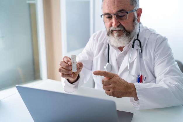 Nahaufnahme eines leitenden arztes, der eine videokonferenz mit einem patienten führt, der das ergebnis des pcr-tests zeigt Premium Fotos