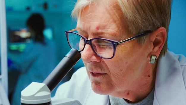 Nahaufnahme eines leitenden wissenschaftlers, der mit dem mikroskop forscht, während kollegen in einem modern ausgestatteten labor am hintergrund arbeiten