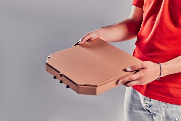 Nahaufnahme eines lieferboten in roter uniform, der eine pizzaschachtel auf grauem hintergrund hält.