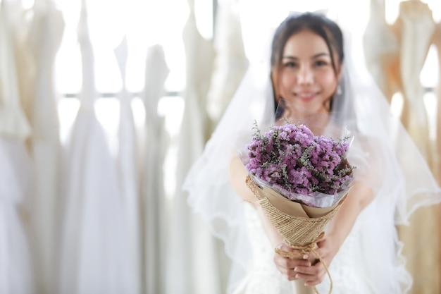 Nahaufnahme eines lila hochzeitsblumenstraußes, der in den händen einer asiatischen schönen braut in weißem kleid mit durchsichtigem haarschleier gehalten wird und lächelnder blick in die kamera in unscharfem hintergrund in der umkleidekabine steht.