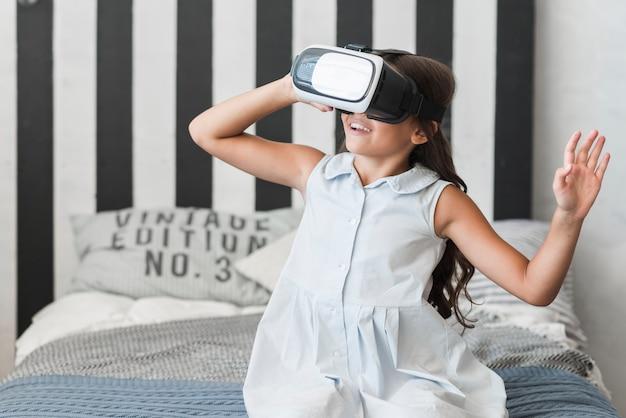 Nahaufnahme eines mädchens, das auf tragenden schutzbrillen der virtuellen realität des betts sitzt