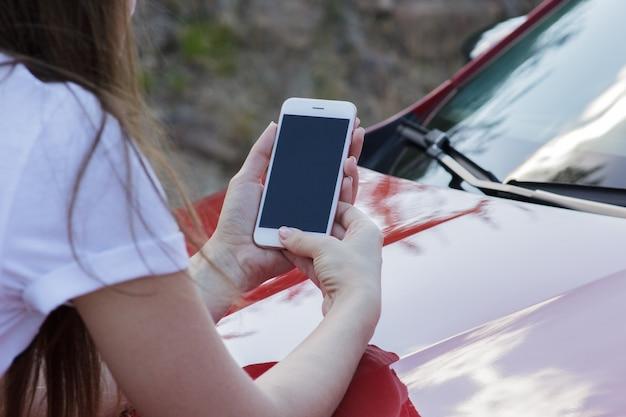 Nahaufnahme eines mädchens, das einen smartphone auf der haube eines autos hält