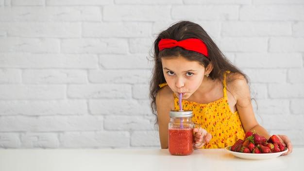 Nahaufnahme eines mädchens, das erdbeeresmoothiesglas trinkt