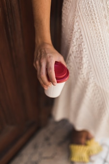 Nahaufnahme eines mädchens, das in der hand wegwerfkaffeetasse hält