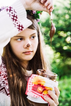 Nahaufnahme eines mädchens, das schokolade vom löffel im glas tropfend hält