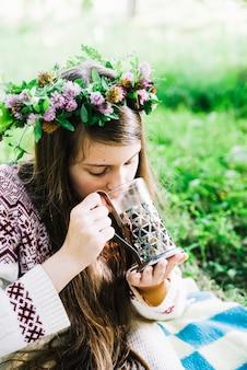 Nahaufnahme eines mädchens, das tragendes glas des kranzes schokoladengetränke trägt