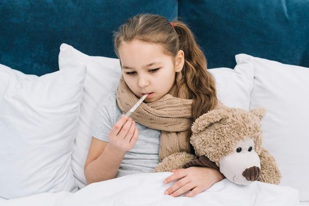 Nahaufnahme eines mädchens, das unter der kälte leidet, die den thermometer in ihren mund einfügt, der auf bett mit weichem spielzeug sitzt
