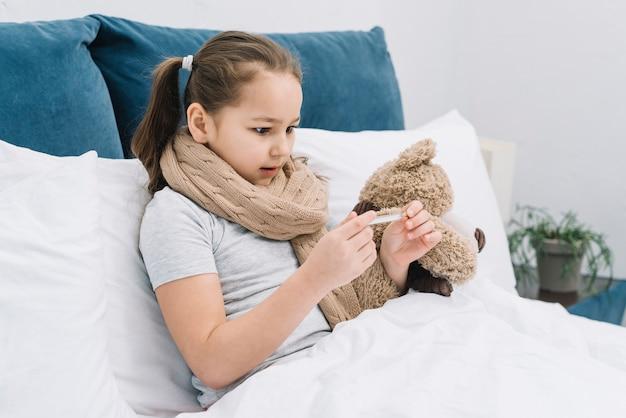 Nahaufnahme eines mädchens, das unter der kälte und dem fieber leidet, die die temperatur thermometer betrachten
