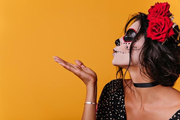 Nahaufnahme eines mädchens im profil. dame mit nicht standardmäßigem make-up zum festival schickt luftkuss