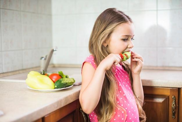 Nahaufnahme eines mädchens, welches die salataufsteckspindel steht in der küche isst