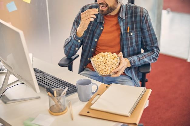 Nahaufnahme eines männlichen arbeiters, der einen knusprigen maissnack genießt, während er mit computer, dokumenten und einer tasse kaffee am tisch sitzt