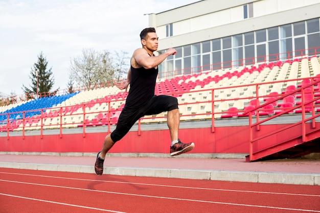Nahaufnahme eines männlichen athleten, der auf rennstrecke am stadion läuft
