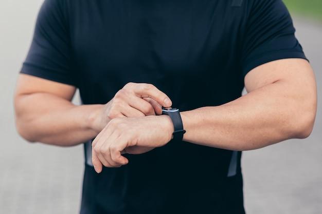 Nahaufnahme eines männlichen athleten, der ein sportprogramm auf einem fitnessarmband auswählt
