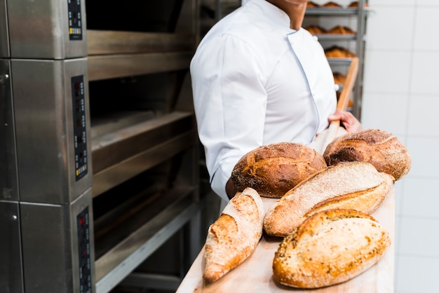 Nahaufnahme eines männlichen bäckers, der frisches gebackenes brot auf hölzerner schaufel vom ofen hält