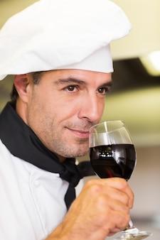 Nahaufnahme eines männlichen chefs, der rotwein riecht