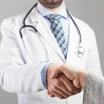 Nahaufnahme eines männlichen doktors, der hand mit patienten gegen grauen hintergrund rüttelt