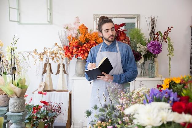 Nahaufnahme eines männlichen floristen, der blumenblumenstraußschreiben im tagebuch mit stift betrachtet