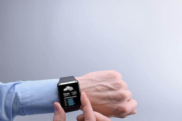 Nahaufnahme eines männlichen geschäftsmannmanns, der wetter auf smartwatch-app-programm auf einem hintergrund des blauen himmels mit weißen wolken prüft