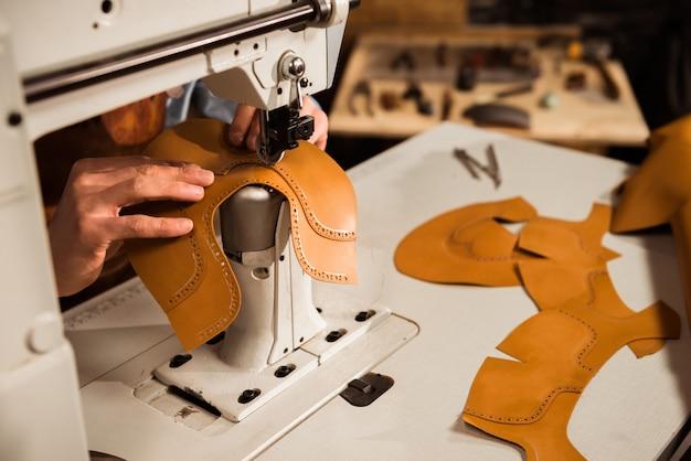 Nahaufnahme eines männlichen handwerkers, der lederteile näht
