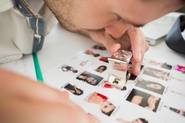 Nahaufnahme eines männlichen künstlers des fokus, der fotos betrachtet