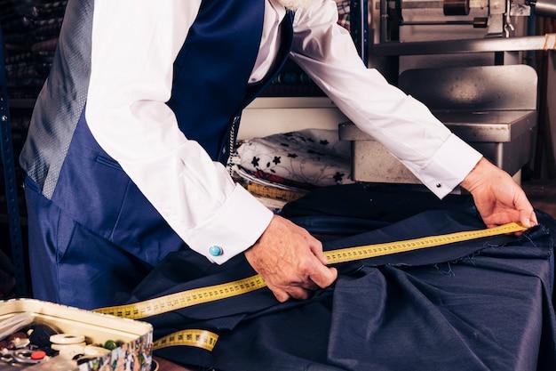 Nahaufnahme eines männlichen schneiders, der maß des gewebes mit gelbem messendem band nimmt