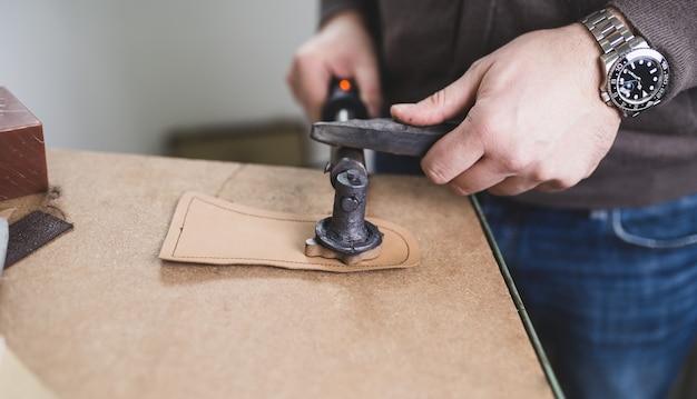 Nahaufnahme eines männlichen schuhmachers, der in seiner werkstatt mit ledertextilien arbeitet. Premium Fotos