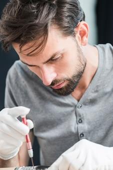 Nahaufnahme eines männlichen technikers, der defekten handy repariert