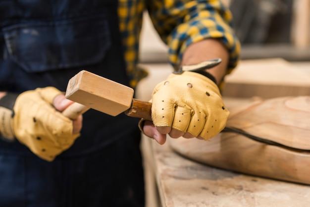 Nahaufnahme eines männlichen tischlers, der meißel auf hölzerner struktur mit hammer schlägt