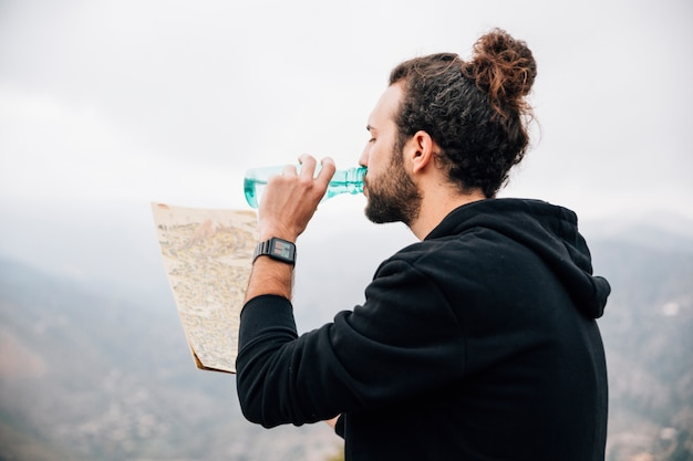 Nahaufnahme eines männlichen wanderers, der die karte trinkt das wasser von der flasche betrachtet