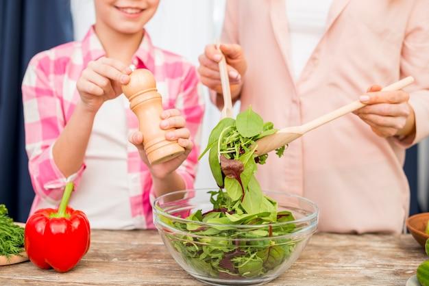 Nahaufnahme eines mahlenden pfeffers des mädchens in die salatschüssel vorbereitet von ihrer mutter