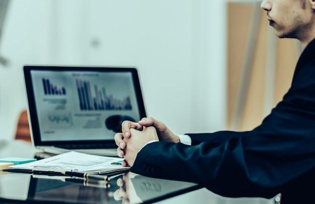 Nahaufnahme eines managers des unternehmens, der vor dem offenen laptop sitzt und mit finanzinformationen arbeitet