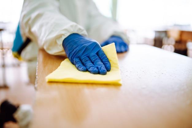 Nahaufnahme eines mannes aus der desinfektionsgruppe räumt den schreibtisch in der schule mit einem gelben lappen auf. professioneller arbeiter sterilisiert das klassenzimmer, um die ausbreitung von covid-19 zu verhindern. gesundheitsversorgung von schülern und studenten.