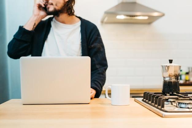 Nahaufnahme eines mannes, der am handy mit laptop und weißem becher auf küchenarbeitsplatte spricht