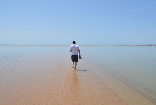 Nahaufnahme eines mannes, der an einem sonnigen tag am strand spazieren geht