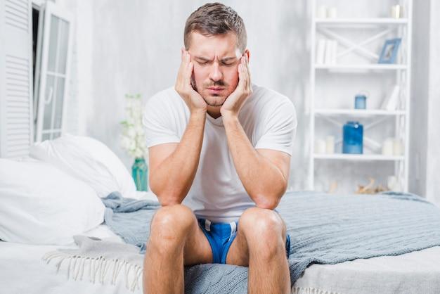 Nahaufnahme eines mannes, der auf dem bett hat kopfschmerzen sitzt