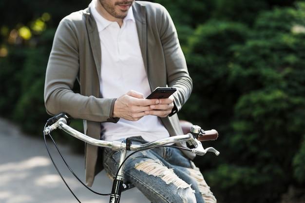 Nahaufnahme eines mannes, der auf dem griff des fahrrades unter verwendung des handys sitzt