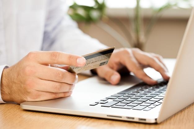 Nahaufnahme eines mannes, der auf einem laptop tippt und eine kreditkarte hält