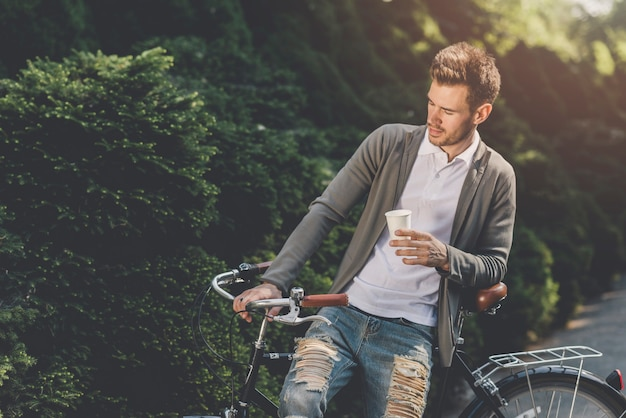 Nahaufnahme eines mannes, der auf fahrrad mit wegwerfkaffeetasse sitzt