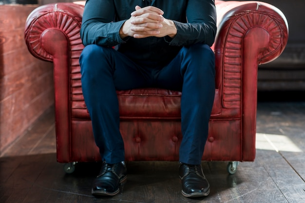 Nahaufnahme eines mannes, der auf lehnsessel mit seiner hand umklammert sitzt