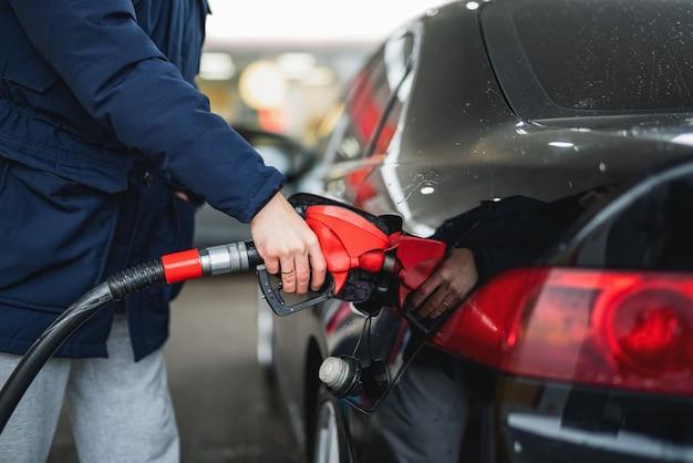 Nahaufnahme eines mannes, der benzin in ein auto an einer tankstelle pumpt.