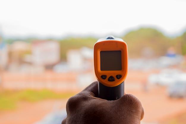 Nahaufnahme eines mannes, der bereit ist, ein infrarot-stirnthermometer (thermometerpistole) zu verwenden, um die körpertemperatur auf virussymptome zu überprüfen - konzept des epidemischen virusausbruchs