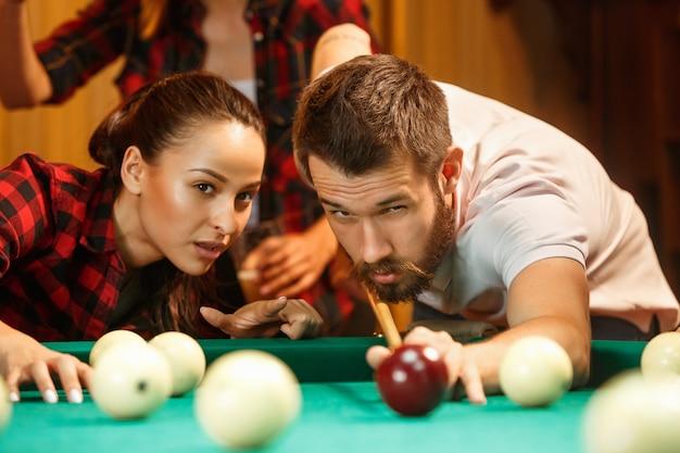 Nahaufnahme eines mannes, der billard spielt. kaukasisches modell, das sorgfältig und anstrengend mit dem stichwort im ball zielt. spielkonzept