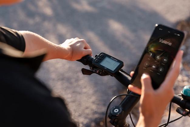 Nahaufnahme eines mannes, der das telefon benutzt, während er auf dem elektrofahrrad ist