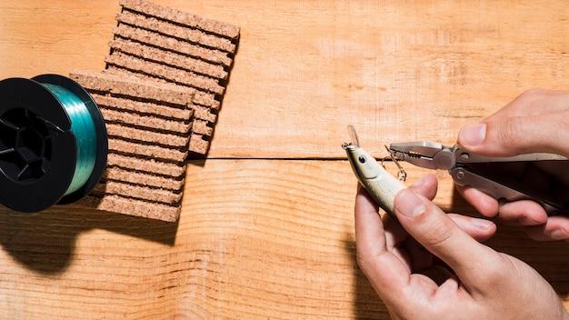 Nahaufnahme eines mannes, der den haken mit zange nahe dem spulen- und korkenbrett auf hölzernem schreibtisch repariert