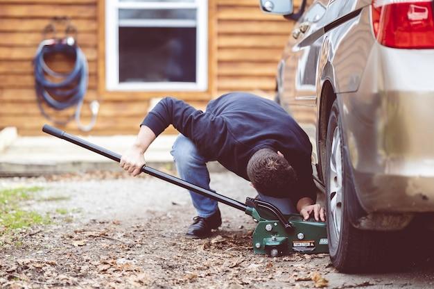 Nahaufnahme eines mannes, der ein auto mit einem werkzeug repariert