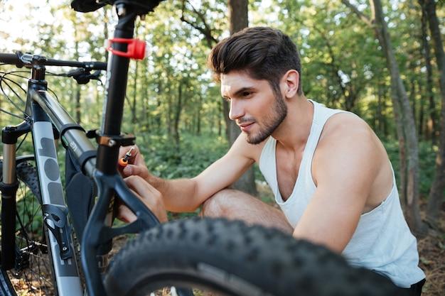 Nahaufnahme eines mannes, der ein fahrrad im wald repariert?