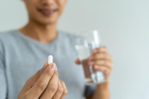 Nahaufnahme eines mannes, der ein nahrungsergänzungsmittel oder ein medikament und ein glas wasser hält, das bereit ist, medikamente einzunehmen. gesundheitskonzepte der menschen.